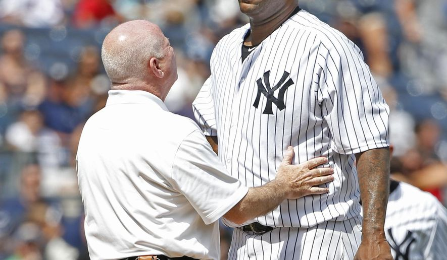 New York Yankees trainer Steve Donohue, left, talks to New York Yankees starting pitcher CC Sabathia on the mound in the third inning before New York Yankees manager Joe Girardi removed Sabathia from the baseball game against the Cleveland Indians at Yankee Stadium in New York, Sunday, Aug. 23, 2015. (AP Photo/Kathy Willens)