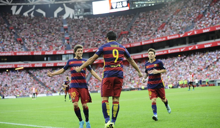 FC Barcelona's  Luis Suarez of Uruguay, center, celebrates his goal with his fellow teammate  Sergi Carnicer, and Lionel Messi of Argentinaafter scoring against Athletic Bilbao soccer team during their Spanish La Liga soccer match,  at San Mames stadium in Bilbao, northern Spain, Sunday, Aug. 23, 2015. (AP Photo/Alvaro Barrientos)