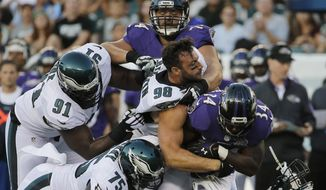 Philadelphia Eagles' Connor Barwin (98) loses his helmet as he combines with Emmanuel Acho (51), Vinny Curry (75) and Fletcher Cox (91) to tackle Baltimore Ravens' Lorenzo Taliaferro (34) during the first half of a preseason NFL football game, Saturday, Aug. 22, 2015, in Philadelphia. (AP Photo/Michael Perez)