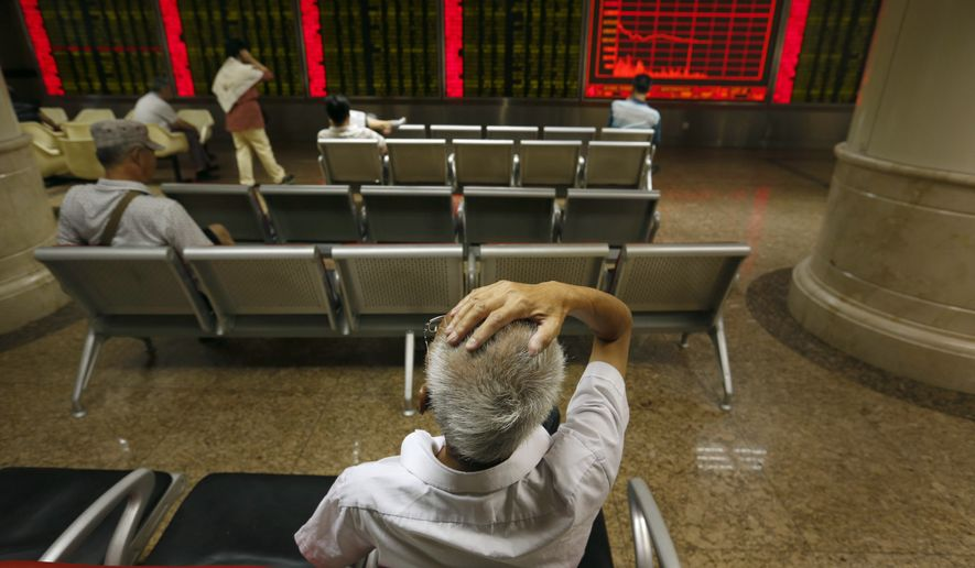 Chinese investors monitor stock prices at a brokerage house in Beijing, Monday, Aug. 24, 2015. Stocks tumbled across Asia on Monday as investors shaken by the sell-off last week on Wall Street unloaded shares in practically every sector. (AP Photo/Mark Schiefelbein)