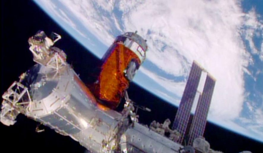 In a photo provided by NASA, a cargo ship from a Japanese company is bolted into place on the International Space Station Monday, Aug. 24, 2015. A Japanese company known for its whiskey and other alcoholic beverages included five types of distilled spirits in the cargo ship that arrived at the space station Monday. (NASA via AP)
