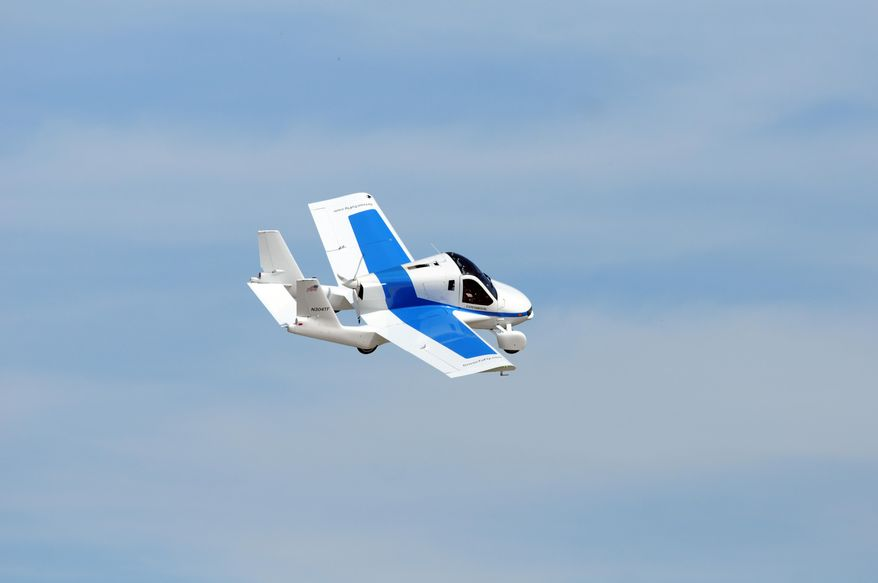 """In this Monday, July 29, 2013 photo, the Terrafugia """"roadable plane"""" flies during the Experimental Aircraft Association's AirVenture in Oshkosh, Wis.  Terrafugia, a privately backed startup in Woburn, Massachusetts, admits on its website that flying cars have become a pop-culture symbol for dreams that don't come true. CEO Carl Dietrich wants to change that. (Joe Sienkiewicz/The Oshkosh Northwestern via AP) NO SALES; MANDATORY CREDIT"""