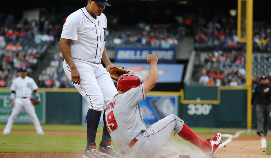 Los Angeles Angels' David Murphy (19) scores as Detroit Tigers starting pitcher Alfredo Simon looks down after throwing a wild pitch to allow the run during the first inning of a baseball game Tuesday, Aug. 25, 2015, in Detroit. (AP Photo/Paul Sancya)