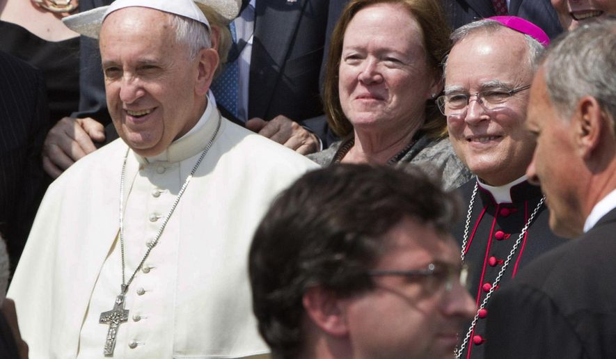 In this Wednesday, June 24, 2015 file photo, Philadelphia's Archbishop Charles Chaput, right, stands next to Pope Francis as they pose for a photo with a delegation from Philadelphia at the end of the pontiff's weekly general audience in St. Peter's Square at the Vatican. Pope Francis will be traveling to Philadelphia in September to attend the World Meeting of Families. Chaput, the meeting's host, is moving to limit lesbian, gay, bisexual and transgender Roman Catholics as they try to lobby for a broader role in the event. (AP Photo/Riccardo De Luca)