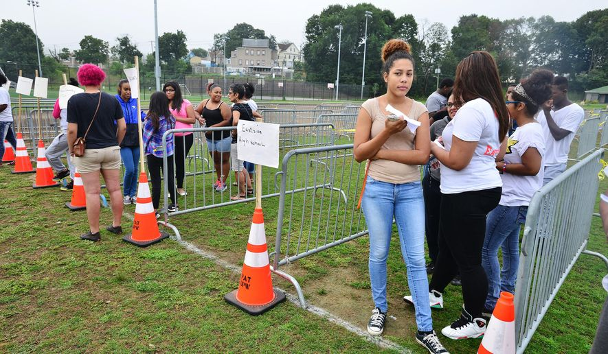 East Side high school student Sahony Frias, right, waits in line for handout tickets to see a Fetty Wap concert at Pennington Park, Monday, Aug. 24, 2015, in Paterson, N.J. Two girls suffered minor injuries on Sunday after Wap jumped off stage and into the crowd at the Billboard Hot 100 festival on Long Island. (Marko Georgiev/The Record of Bergen County via AP) ONLINE OUT; MAGS OUT; TV OUT; INTERNET OUT;  NO ARCHIVING; MANDATORY CREDIT