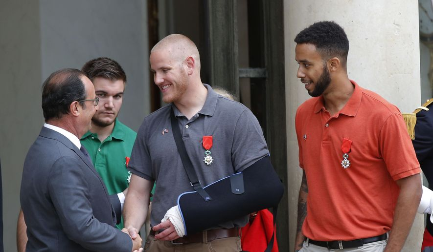 French President Francois Hollande bids farewell to U.S. Airman Spencer Stone as U.S. National Guardsman Alek Skarlatos of Roseburg, Ore., second from left, and Anthony Sadler, a senior at Sacramento State University in California, right, look on at the Elysee Palace in Paris, France, after Hollande awarded them with the French Legion of Honor on Monday, Aug. 24, 2015. (AP Photo/Michel Euler)