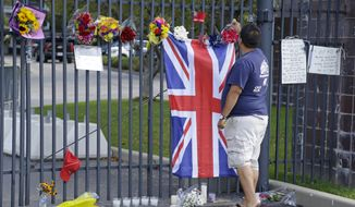 Jerry Perez, of Indianapolis, places a flower on the main gate of the Indianapolis Motor Speedway in a memorial to race driver Justin Wilson, of England, Tuesday, Aug. 25, 2015, in Indianapolis. Wilson died from a head injury suffered when a piece of debris struck him at Pocono Raceway. He was 37. (AP Photo/Michael Conroy)
