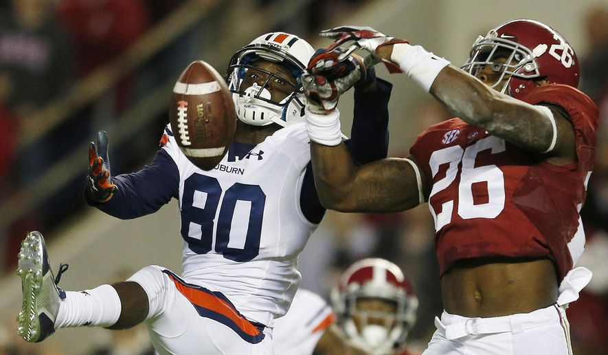 In this Nov. 29, 2014, file photo, Alabama defensive back Landon Collins (26) breaks up a pass meant for Auburn wide receiver Marcus Davis (80) during the first half of the Iron Bowl NCAA college football game in Tuscaloosa, Ala. Go into the bowl season with a chance to win the national championship. That's mostly been the case in recent years and no reason to think it won't happen again for these two teams. College football's most intense in-state rivalry has been wild the past two seasons with the Kick-6 going Auburn's way in 2013 and then a record-setting shootout being won by Alabama in 2015. The teams will meet Nov. 28, 2015 at Auburn. (AP Photo/Butch Dill, File)