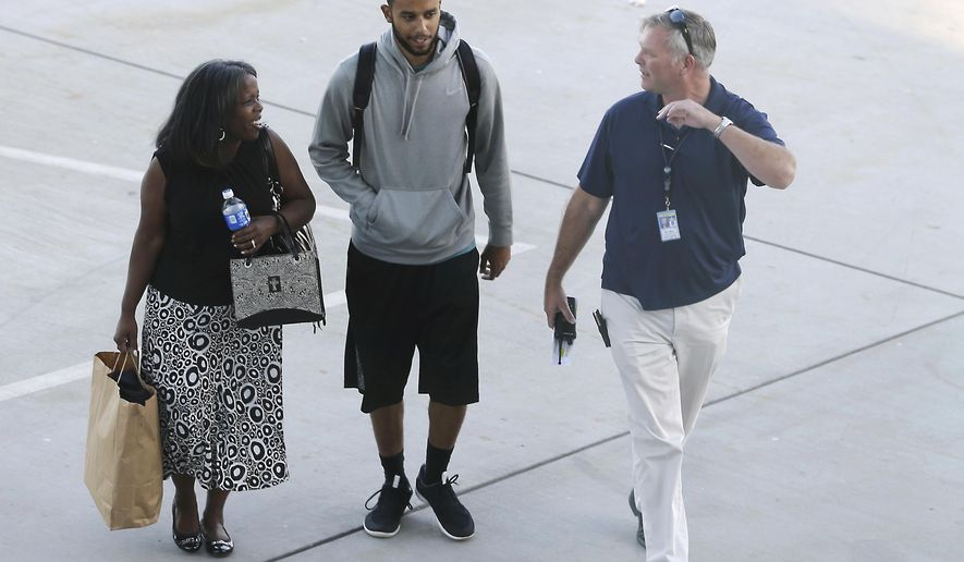 Anthony Sadler, center, who helped stop a terror attack on a high-speed train traveling from Amsterdam to Paris, walks across the tarmac to a waiting vehicle at Sacramento International Airport, Tuesday, Aug. 25, 2015, in Sacramento, Calif. Sadler and two Sacramento-area friends, U.S. Air Force Airman Spencer Stone, and Oregon National Guardsman Alek Skarlatos, helped subdue Ayoub El-Khazzani, a man with ties to radical Islam who was carrying a handgun and an assault weapon on the train Friday. (AP Photo/Rich Pedroncelli)