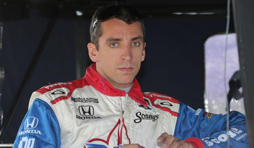 FILE - This is a June 1, 2014, file photo showing Justin Wilson waiting to qualify before the second race of the IndyCar Detroit Grand Prix auto racing doubleheader in Detroit. The IndyCar Series has bounced from one problem to another all season as it scrambles for viewers and new fans. It heads into the season finale this weekend after suffering the worst possible blow: The death of a driver, with Justin Wilson dead at 37 from injuries suffered in a crash. (AP Photo/Bob Brodbeck, File)