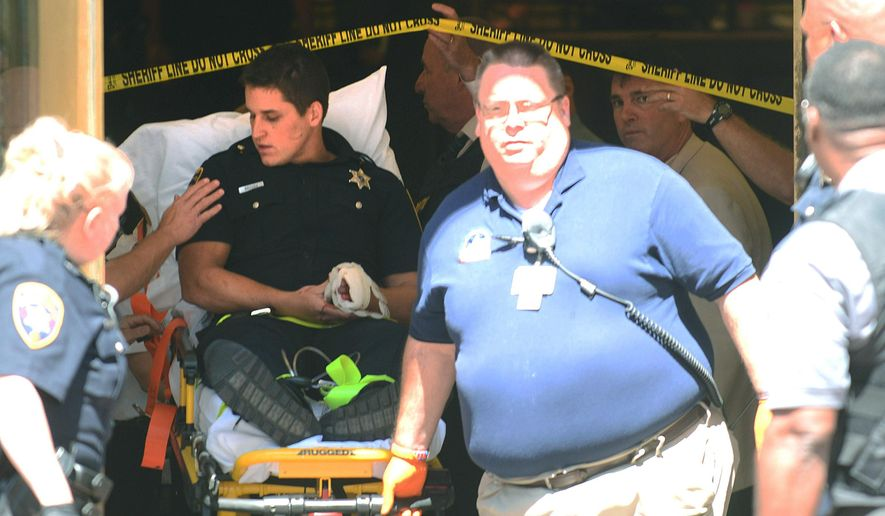 A Chester County sheriff's deputy with a hand injury is taken from the lobby of the Chester County Courthouse following a shooting Tuesday, Aug. 25, 2015, in West Chester, Pa. The Daily Local News of West Chester reports that the shooting involved a member of the Chester County sheriff's office and a man who apparently tried to enter the courthouse.  (Pete Bannan/Daily Local News via AP)