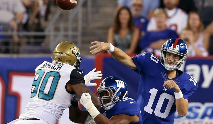 New York Giants quarterback Eli Manning (10) throws a pass over Jacksonville Jaguars' Andre Branch (90) during the first half of a preseason NFL football game Saturday, Aug. 22, 2015, in East Rutherford, N.J. (AP Photo/Adam Hunger)