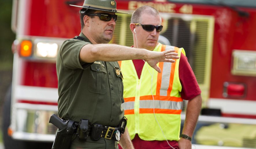 """A West Virginia State Police Officer speaks with officials to shut down Route 250 that runs in front of Philip Barbour High School in Philippi, W.v., after a """"hostage-like"""" situation occurred in the cafeteria of the school. (Associated Press)"""