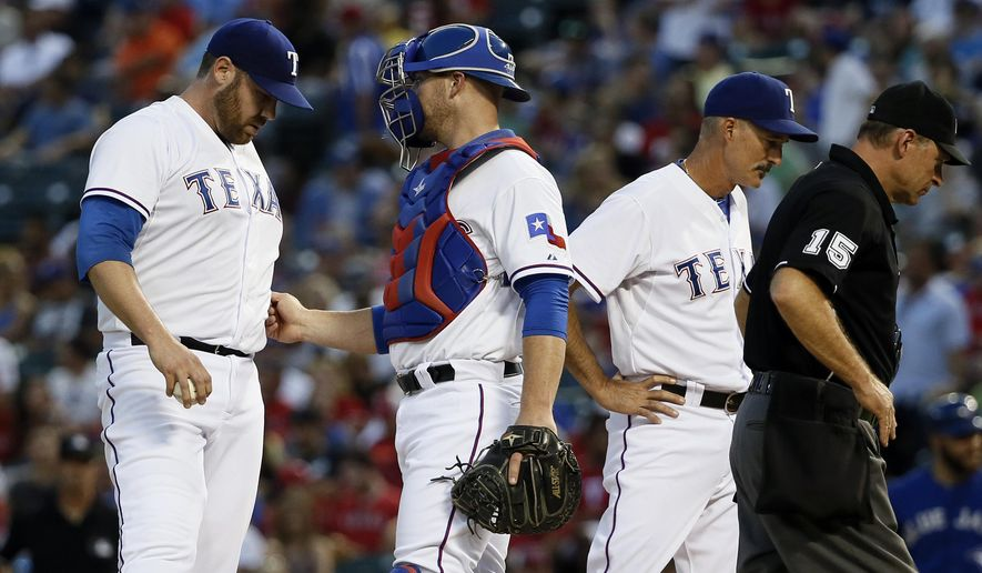 Texas Rangers' Colby Lewis, left, talks with catcher Chris Gimenez, second from left, as Rangers pitching coach Mike Maddux and umpire Ed Hickox, right, walk off the mound during the third inning of a baseball game against the Toronto Blue Jays on Wednesday, Aug. 26, 2015, in Arlington, Texas. (AP Photo/Tony Gutierrez)