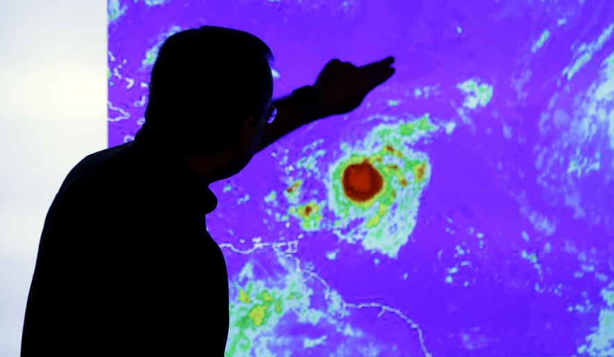 James Franklin, chief hurricane forecaster, looks at an image of Tropical Storm Erika as it moves westward towards islands in the eastern Caribbean, at the National Hurricane Center, Wednesday, Aug. 26, 2015, in Miami. Tropical storm warnings have been issued for Puerto Rico, the U.S. and British Virgin Islands, and the Leeward islands. (AP Photo/Lynne Sladky)