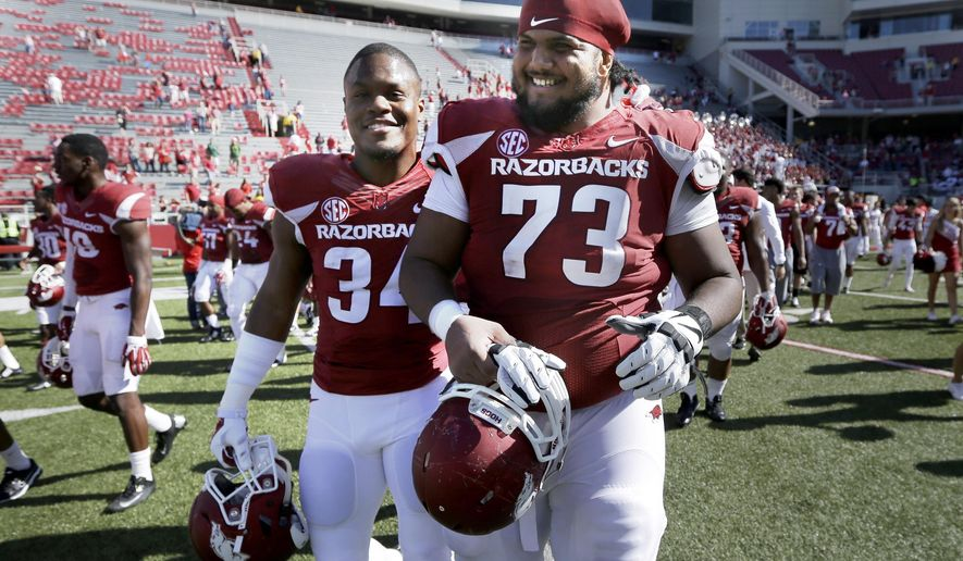FILE - In this Oct. 25, 2014, file photo, Arkansas offensive tackle Sebastian Tretola (73) and linebacker Braylon Mitchell (34) walk off the field after an NCAA college football game against UAB in Fayetteville, Ark. Arkansas offensive lineman Sebastian Tretola is best known nationally for his touchdown pass last season. To Razorbacks coach Bret Bielema, however, the senior might be the most surprising _ and personable _ player he's ever coached. (AP Photo/Danny Johnston, File)