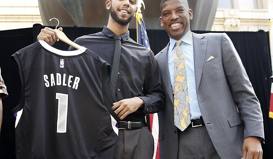 """Anthony Sadler, one of the three Americans that helped stop an alleged terrorist shooting aboard a Paris bound train, displays a Sacramento Kings jersey with his name and number presented to him by Mayor Kevin Johnson at a news conference Wednesday, Aug. 26, 2015, in Sacramento,Calif.  Salder spoke briefly saying it has been a """"crazy last few days.""""(AP Photo/Rich Pedroncelli)"""