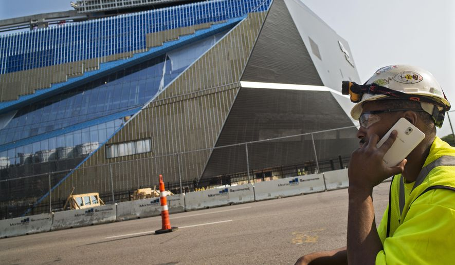 "Apprentice electrician Coshay Murray talks on a phone in front of the Minnesota Vikings' new stadium in Minneapolis, Wednesday, Aug. 26, 2015. A construction worker at the new stadium died and a second worker was seriously injured when they fell Wednesday morning while doing roofing work. Murray  said,""we are all a little traumatized today."" (Richard Tsong-Taatarii/Star Tribune via AP)  MANDATORY CREDIT; ST. PAUL PIONEER PRESS OUT; MAGS OUT; TWIN CITIES LOCAL TELEVISION OUT"