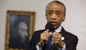 In this May 2, 2015, file photo, a portrait of the Rev. Dr. Martin Luther King Jr. hangs on the wall behind the Rev. Al Sharpton as he speaks during a rally at the National Action Network, in New York. (AP Photo/Mary Altaffer, File)