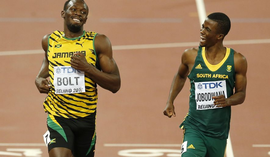 Jamaica's Usain Bolt, left, and South Africa's Anaso Jobodwana laugh after finishing a men's 200m semifinal at the World Athletics Championships at the Bird's Nest stadium in Beijing, Wednesday, Aug. 26, 2015. (AP Photo/Mark Schiefelbein)