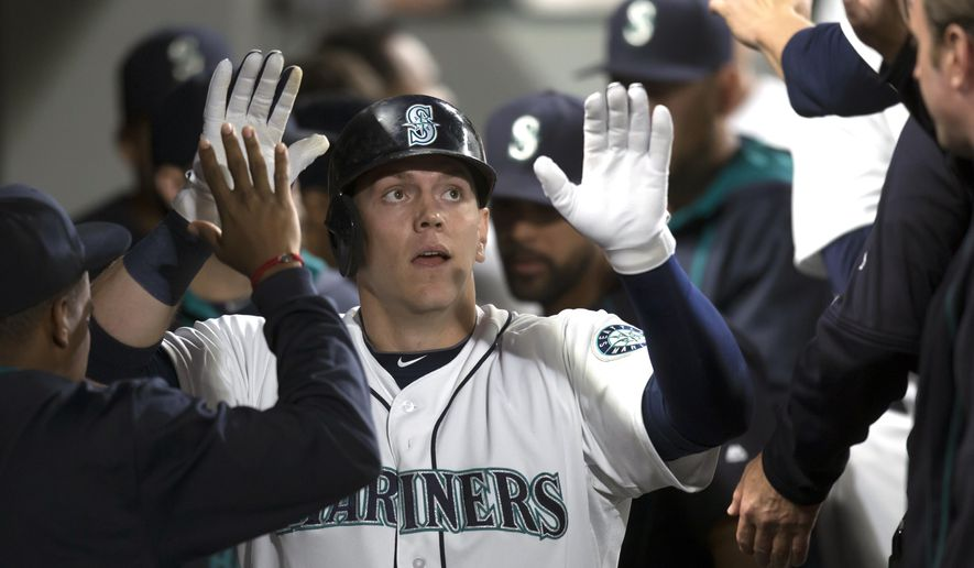 Seattle Mariners Logan Morrison is congratulated by teammates after hitting a two-run home run during the fourth inning of a baseball game against the Oakland Athletics, Tuesday, Aug. 25, 2015, in Seattle. The Mariners won 6-5. (AP Photo/Stephen Brashear)