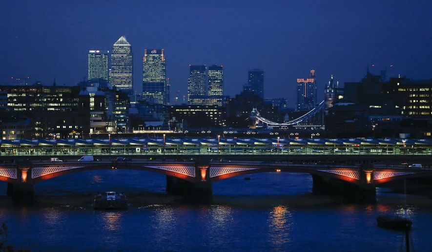 FILE - In this Nov. 5, 2014 file photo, the financial district is lit behind Blackfriars Bridge at dusk over the River Thames in London. This fall business travelers visiting London have a number of evening events, activities and attractions to choose from when their workday commitments are done. (AP Photo/Kirsty Wigglesworth, File)