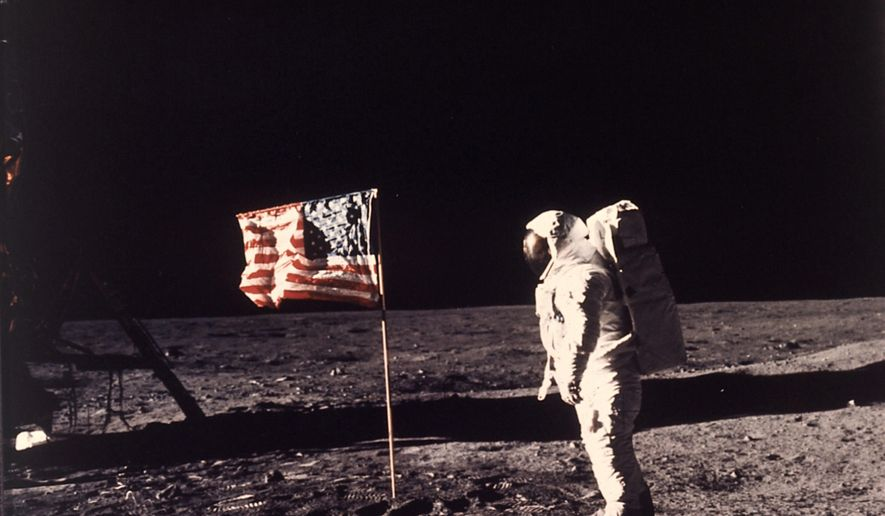 "In this July 20, 1969, file photo, astronaut Edwin E. ""Buzz"" Aldrin Jr. stands next to a U.S. flag planted on the moon during the Apollo 11 mission. (Neil A. Armstrong/NASA via AP)"