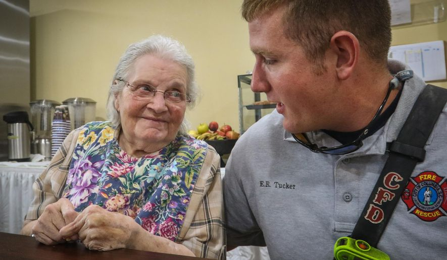 Christine Moore talks with Columbia firefighter Ethan Tucker on Aug. 24, 2015 in Columbia, S.C.  Two months ago, Tucker forced in the door to Moore's apartment on the third floor the Forest Pines retirement community. A three-alarm fire was blazing, and Moore could not walk.  He scooped her up from her bed and carried her over his shoulder to safety.  (Tim Dominick/The State via AP) ALL LOCAL MEDIA OUT, (TV, ONLINE, PRINT); MANDATORY CREDIT