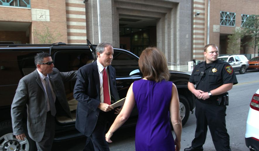 Texas Attorney Gen. Ken Paxton, second left, arrives at the Tarrant County Courthouse for a hearing on his felony securities indictment, Thursday, Aug. 27, 2015, in Fort Worth, Texas. Paxton pleaded not guilty Thursday to charges alleging that he defrauded investors before he became the state's top lawyer, and his attorney Joe Kendall announced that he would no longer represent him.  (Star-Telegram/Rodger Mallison via AP, Pool)