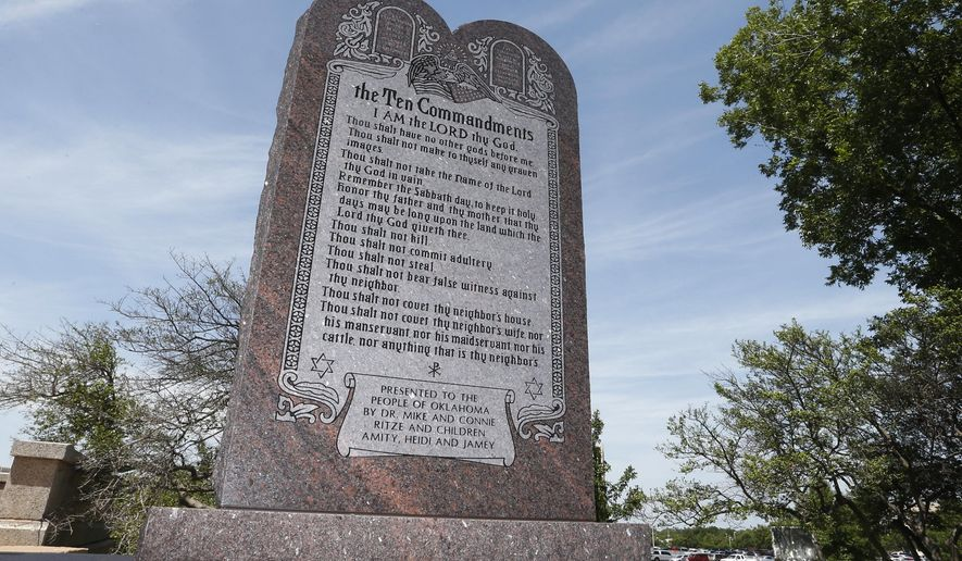 FILE - In this Friday, June 20, 2014 file photo, the Ten Commandments monument is pictured at the state Capitol in Oklahoma City. The Oklahoma Supreme Court Thursday, Aug. 27, 2015 ordered a County judge to implement a ruling that said a Ten Commandments monument on the state Capitol grounds is unconstitutional and must be removed. (AP Photo/Sue Ogrocki, file)