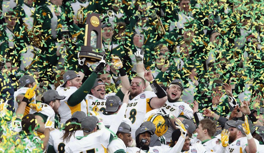FILE - In this Jan. 10, 2015 file photo, members of the North Dakota State football team hold the championship trophy after their 29-27 win over Illinois State in the FCS Championship NCAA college football game in Frisco, Texas.  NDSU says it will start providing stipends to scholarship athletes in all 16 sports beginning next year with a goal of paying the full cost of attending college. Officials with the school that has won four straight Football Championship Subdivision titles say the anticipated additional cost will be up to $3,400 per full scholarship. (AP Photo/Tim Sharp, File)