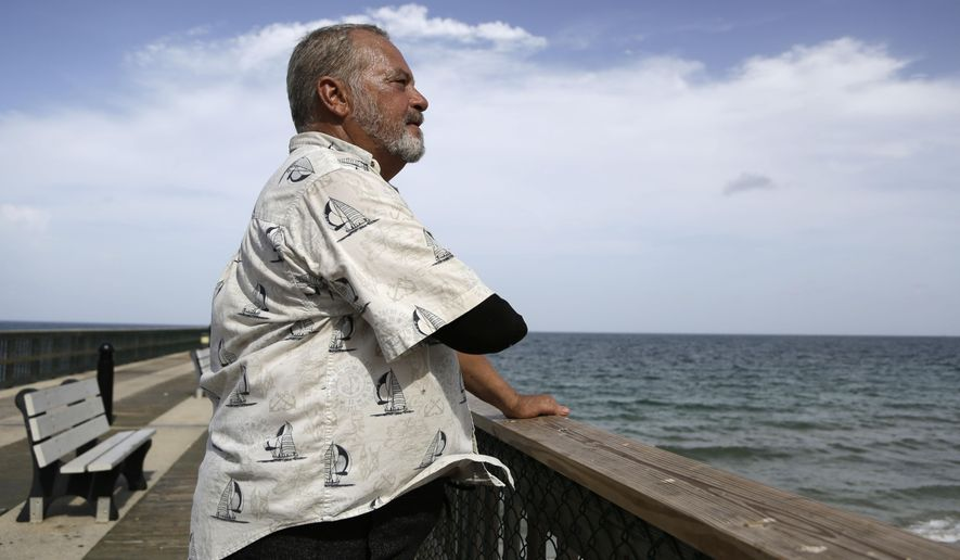 In this Aug. 5, 2015, photo, Al Brennaka, 57, poses for a photograph in Pompano Beach, Fla. Brennaka lost half his arm at age 19 after being attacked by a shark while surfing off Daytona Beach. Despite his injury, Brennaka is one of more than a dozen attack survivors who have become shark advocates, trying to educate the public about sharks' declining populations and their importance to ocean ecosystems. (AP Photo/Lynne Sladky)