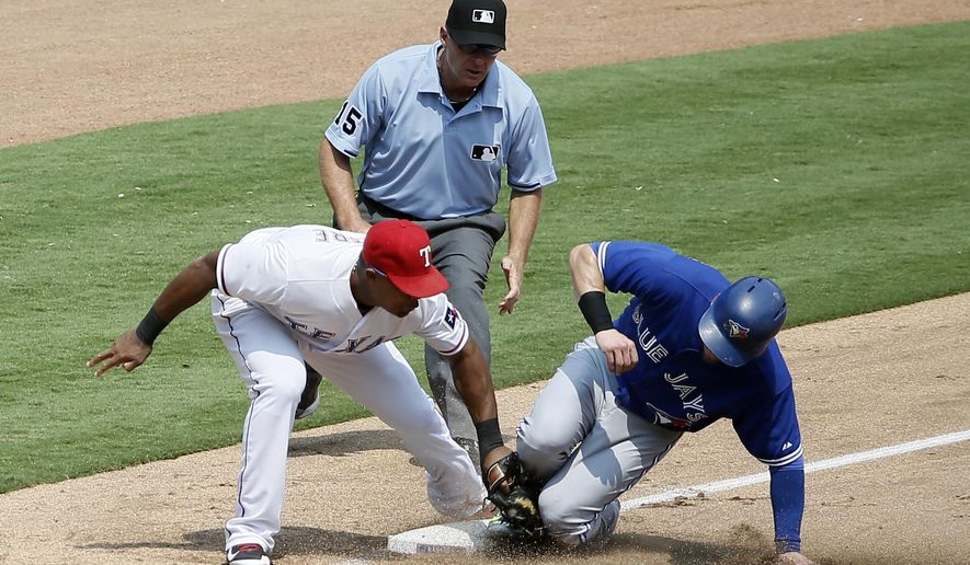 Texas Rangers third baseman Adrian Beltre, left, is unable to tag out Toronto Blue Jays' Josh Donaldson, right, who steals the bag as umpire Ed Hickox, center, watches in the sixth inning of a baseball game Thursday, Aug. 27, 2015, in Arlington, Texas. (AP Photo/Tony Gutierrez)