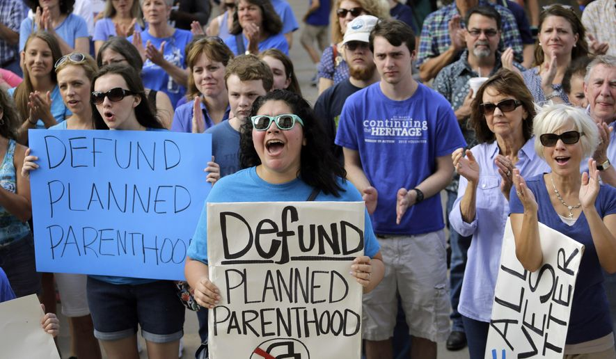 """FILE- In this July 28, 2015 file photo, Erica Canaut, center, cheers as she and other anti-abortion activists rally on the steps of the Texas Capitol in Austin, Texas to condemn the use in medical research of tissue samples obtained from aborted fetuses.  Planned Parenthood Federation of America held a conference call Thursday, Aug. 27, 2015, to discuss what it calls a """"smear campaign"""" against the organization and its affiliates by a California-based anti-abortion group. (AP Photo/Eric Gay, File)"""