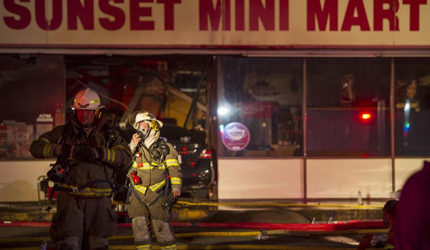 Local fire departments work the scene of a fire at the Sunset Mini Mart convenience store in Sunset, La., where a suspect drove into the front facade of the building before a standoff with the police Wednesday, Aug. 26, 2015. The man barricaded himself in the store following a fatal incident. (Paul Kieu/The Daily Advertiser via AP)  NO SALES; MANDATORY CREDIT