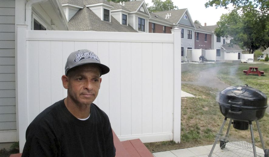 Luis Vazquez, a 49-year-old Navy veteran who was homeless off and on for 10 years, sits outside his home in a veterans' housing complex Thursday, Aug. 27, 2015, in Newington, Conn. U.S. Veterans Affairs Secretary Robert McDonald and Connecticut officials were at the housing complex Thursday to announce that the state is the first in the country to end chronic homelessness among veterans. (AP Photo/Dave Collins)