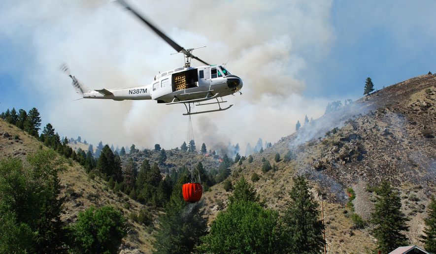 This August 2008 photo provided by the Montana Dept. of Natural Resources and Conservation shows a firefighting helicopter making a water drop over the Pump House Fire in western Montana. U.S. aviation experts are planning to head to Montana to review the state's firefighting protocols and see for themselves whether its helicopters should be used to attack blazes on federal lands, officials said Thursday, Aug. 27, 2015. (Montana Dept. Natural Resources and Conservation via AP)