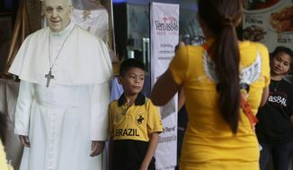 "Filipinos have their photos taken with a cutout of Pope Francis at SM Mall of Asia, one of the country's largest shopping malls, Wednesday, Sept. 10, 2014 at suburban Pasay city, south of Manila, Philippines. In Asia's bastion of Roman Catholic faith, images of Pope Francis are getting the K-pop treatment. Life-size cardboard cutouts are being distributed to churches, schools and malls in the Philippine capital to generate ""papal fever"" before the pope's visit. (AP Photo/Bullit Marquez)"
