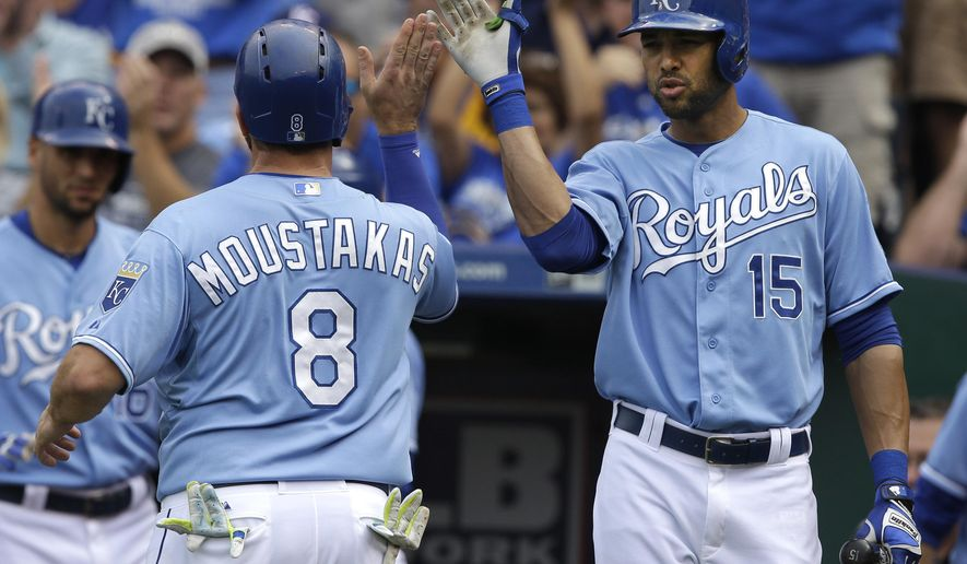 Kansas City Royals' Mike Moustakas (8) is congratulated by on-deck batter Alex Rios (15) after scoring on a single by teammate Salvador Perez during the fourth inning of a baseball game against the Baltimore Orioles at Kauffman Stadium in Kansas City, Mo., Thursday, Aug. 27, 2015. (AP Photo/Orlin Wagner)