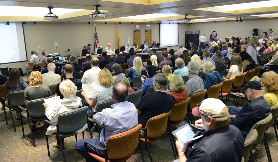 A capacity crowd attended the New Mexico Department of Game and Fish Commission meeting to give public comments concerning the commissioner vote Thursday, Aug. 27, 2015 at the Santa Fe Community College in Santa Fe, N.M.  The New Mexico Game Commission has approved new hunting limits for bears and cougars around the state despite the protests of environmental groups.  (Clyde Mueller/Santa Fe New Mexican via AP) MANDATORY CREDIT