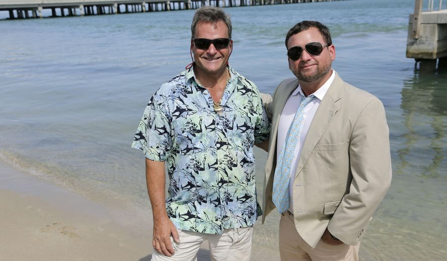 In this Aug. 3, 2015 photo, Kent Bonde, left, and Mike Beach, right, pose for a photograph in Key Biscayne, Fla. Both are survivors of shark attacks, and are now shark advocates, trying to educate the public about sharks' declining populations and their importance to ocean ecosystems. (AP Photo/Lynne Sladky)