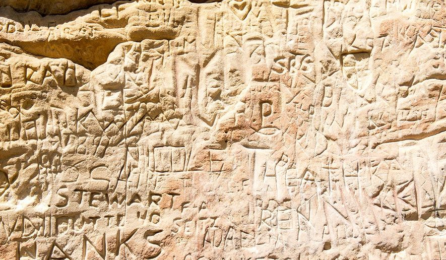 Inscriptions cover the face of History Rock in Hyalite Canyon south of Bozeman, Mont., Aug. 11, 2015.  Of all the great day hikes in Hyalite Canyon, the 2.4-mile round trip route to History Rock is one of the finest. (Ben Pierce/The Bozeman Daily Chronicle via AP) MANDATORY CREDIT