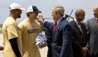 In this Aug. 8, 2008, file photo, President George W. Bush is met by Deuce McAllister, left, and Drew Brees of the New Orleans Saints football team as he arrives at Louis Armstrong New Orleans International Airport on the way to events marking the third anniversary of Hurricane Katrina, in Kenner, La. (AP Photo/J. Scott Applewhite, File)
