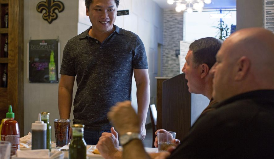 """Restaurant owner Hieu Doan, 41, talks with customers in New Orleans, Monday, Aug. 17, 2015. """"Namese,"""" a Vietnamese restaurant in New Orleans, infuses the famous flavors of New Orleans with traditional Asian favorites.  New Orleans is a city where eating has long been a serious business. But 10 years ago, that seemed imperiled when Hurricane Katrina and the levee breaches that flooded the coast threatened that rich culinary history. (AP Photo/Max Becherer)"""