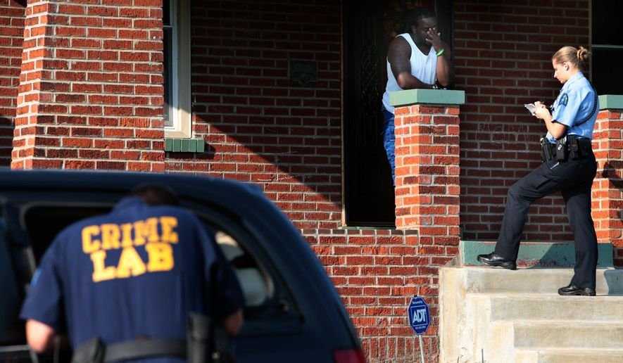 A St. Louis police officer interviews a witness to the shooting of a child in the 4800 block of Bessie Avenue in the Penrose neighborhood, Thursday, Aug. 27, 2015 in St. Louis, Mo. A 3-year-old St. Louis boy is in stable condition after being shot — the third shooting involving a child in the region since last week. (Robert Cohen/St. Louis Post-Dispatch via AP)  EDWARDSVILLE INTELLIGENCER OUT; THE ALTON TELEGRAPH OUT; MANDATORY CREDIT