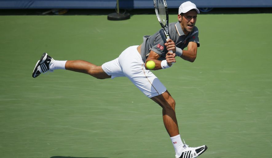 ADVANCE FOR WEEKEND EDITIONS, AUG. 29-30 - FILE -  In this Aug. 23, 2015, file photo, Novak Djokovic, of Serbia, serves the ball to Roger Federer, of Switzerland, during a final match at the Western & Southern Open tennis tournament in Mason, Ohio. Djokovic is the No. 1 seed for the 2015 U.S. Open. Federer is seeded second. (AP Photo/John Minchillo, File)