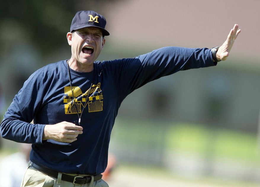 Michigan football coach Jim Harbaugh yells during the Coach Jim Harbaugh's Elite Summer Football Camp, Friday, June 5, 2015, at Prattville High School in Prattville, Ala. Harbaugh will have to improve the Wolverines by one game over last season to get them into postseason. (Albert Cesare/The Montgomery Advertiser via AP)  NO SALES; MANDATORY CREDIT
