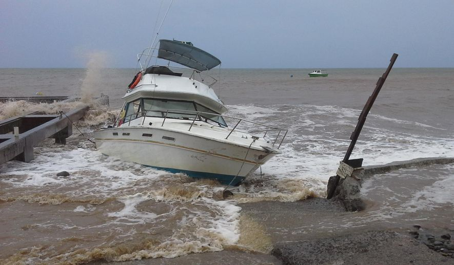 A boat sits in shallow water as Tropical Storm Erika passes through New Town, Dominica, Thursday, Aug. 27, 2015. (AP Photo/Carlisle Jno Baptiste) ** FILE **