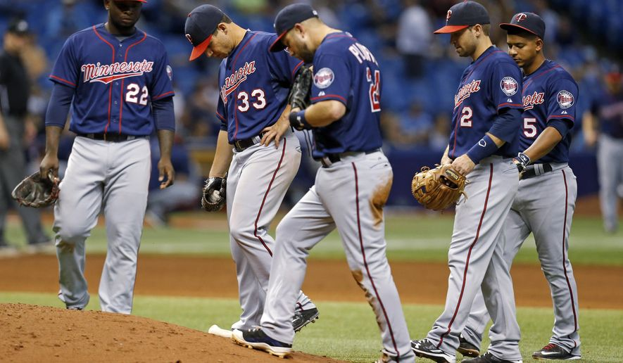 Minnesota Twins relief pitcher Neal Cotts (33) is joined by teammates, from left, Miguel Sano (22), Trevor Plouffe (24), Brian Dozier (2) and Eduardo Escobar (5) during the sixth inning of a baseball game against the Tampa Bay Rays on Thursday, Aug. 27, 2015, in St. Petersburg, Fla. The Rays won 5-4. (AP Photo/Mike Carlson)