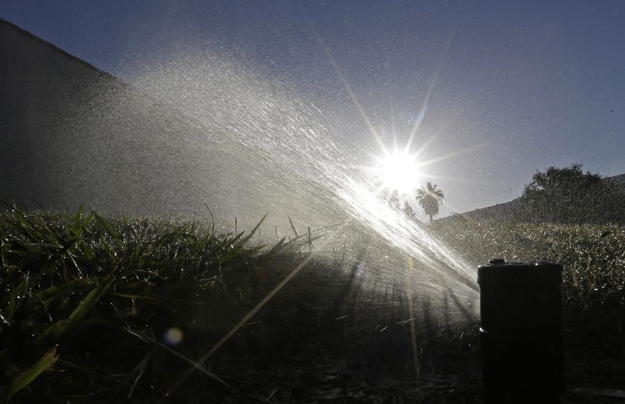 FILE - In this June 23, 2015, file photo a lawn is irrigated in Sacramento, Calif. A report is due out Thursday, Aug. 27, 2015 on monthly state water conservation figures. Many California cities are conserving well, and officials are turning their attention to the few cities/agencies that aren't doing so well. (AP Photo/Rich Pedroncelli, File)